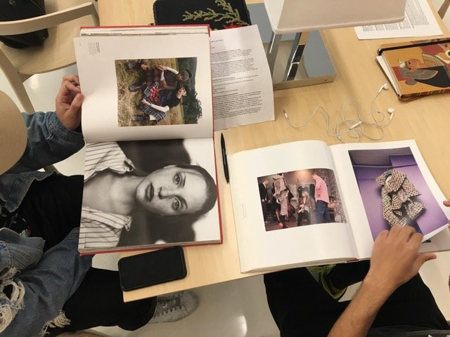 top-down photo of a table with two students reading fashion photography books