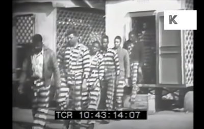 screenshot from the video showing a line of prisoners walking out of a vehicle.