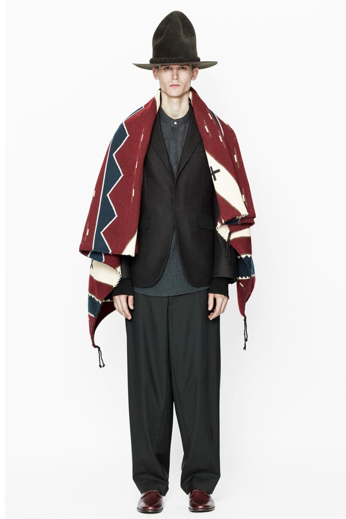 a look from Siki Im's 2011 Fall/Winter collection. The model is dressed in a loose fitting black suit with a red, white and blue Navajo Blanket draped over his shoulders. He wears an oversized dark brown cowboy hat and dark brown shiny dress shoes.