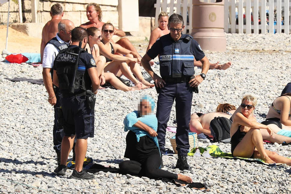 Three French Police officers stand around a woman seated on the beach as she lifts her top to remove it. The woman's face is hidden by a mosaic effect.