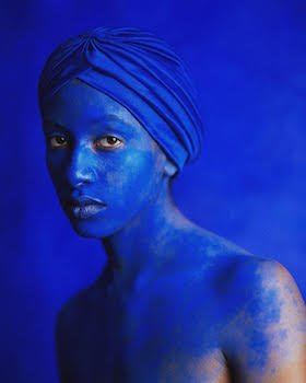 photo of a woman who is covered in blue pigment from her face to her chest