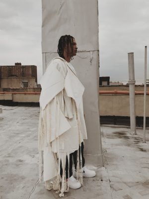artistic photo of a man wearing a dramatically draped white garment