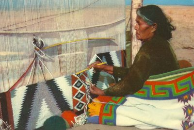 Photo of a Navajo woman sitting with a blanket wrapped around her lower half in front of a traditional upright loom. She is weaving a black, white, grey and red patterned textile in the desert