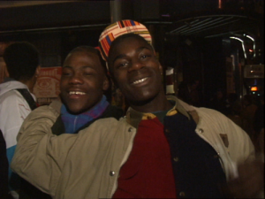 Screenshot from the video showing two young Black men smiling for the camera