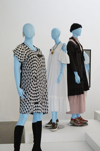 Image of three blue mannequins from the exhibition. The front mannequin is dressed in a black and white printed gown with black high boots. One background mannequin is dressed in a white summer dress and the other is in a red and white pinstriped garment with a lightweight black jacket over top and a black beanie.
