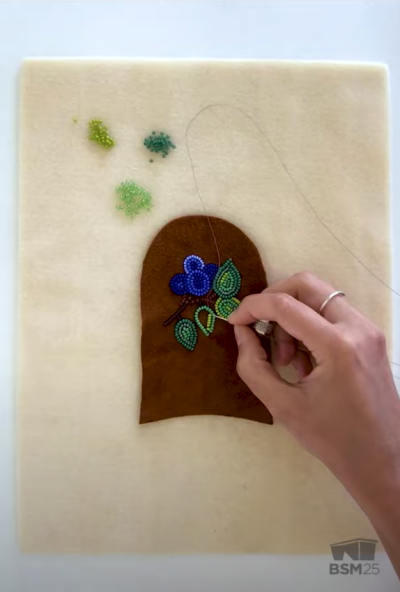 Screenshot from the video showing Justine woods beading a leaf and flower motif onto a piece of the moccasin