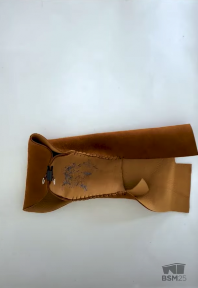 screenshot from the video showing pieces of the inside-out shell of the moccasin pinned together in preparation for sewing