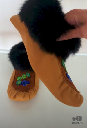 screenshot from the video showing a hand holding up one finished moccasin for the camera to get a closeup view