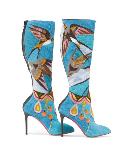 A pair of thigh high stiletto boots on display in front of a black background. Boots are covered in turquoise beads and motifs of swallows and plants