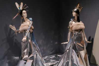 Two mannequins wearing silver reflective dress with fur accents and feather headdresses