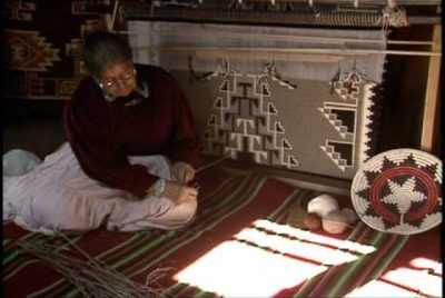 Screenshot from the video showing a Navajo woman in front of a traditional loom preparing the wool to be woven