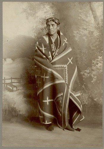 black and white photograph of a Navajo man wearing a traditional blanket draped over his shoulders