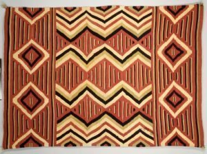 Image of a geometrically patterned red, cream, mustard and black coloured Navajo Blanket