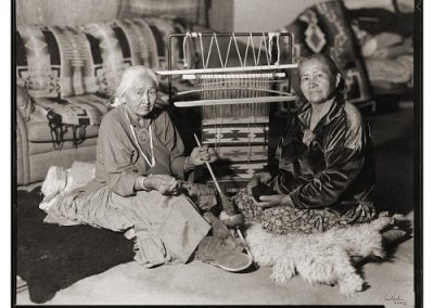 Black and white photograph of two elderly Navajo women sitting in front of a navajo loom on the floor with a partially finished weaving on it.