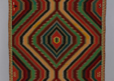 Image of a geometric pattern red, maroon, green, mustard, brown and black Navajo Blanket