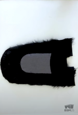 Screenshot from the moccasin making video showing two cut out pieces of fur layered on top of one another