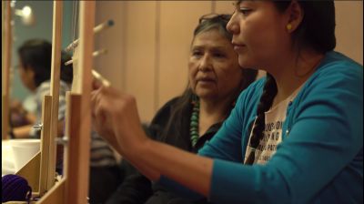 Screenshot from the video showing a Navajo woman at a loom with another woman behind her overlooking her work