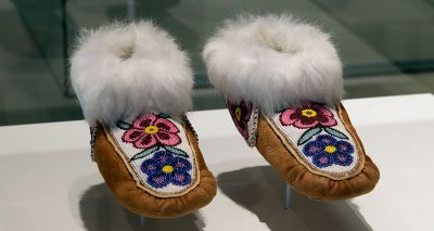 A pair of moccasins sits in a white display case. The moccasins have pink and purple beaded flowers on the vamp of the shoe and white fur cuffs