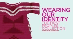 "The exhibition poster featuring pink text which reads ""wearing our identity, the first peoples collection permanent exhibition"" on a pale blue background. To the left of the text is a maroon first nation's tunic with two white stripes across the chest and arms"