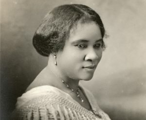 Sepia-toned portrait photo of Madam C.J. Walker facing slightly right. She looks off-camera with a hint of smile.
