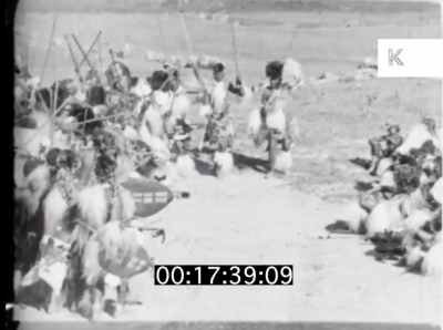 still image from the archival footage showing male tribe members on one side of a field facing towards the women on the right side of the field