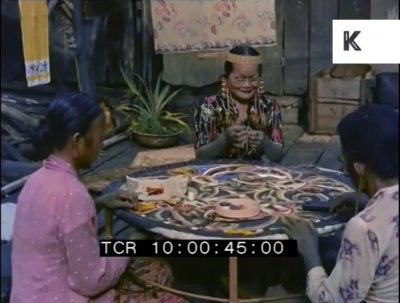 still image form the archival footage showing three tribal women from Borneo sitting around a table completing crafts