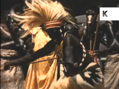 Still from the archive footage showing a Kenyan man performing the Watussi dance in full regalia