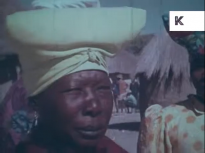 Still image from the archival footage showing an African woman in a headwrap
