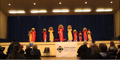 Screenshot from the video showing several young dancers on stage wearing Vietnamese Ao Dai and using the Non La as a prop