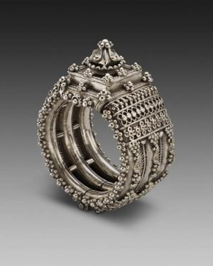 Museum photo of an ornate silver ring on a grey background