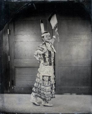 a portrait of a female native american dancer in full regalia