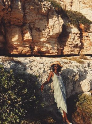 A photograph of a black woman leaning against a rock wall