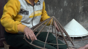 Screenshot from the video showing the frame of a Vietnamese conical hat in a woman's lap