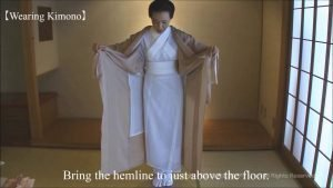 Screenshot from the video showing a woman preparing to wrap the outer Kimono over her undergarments.