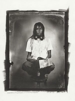 Black and white photograph of a young Native American man holding a magazine