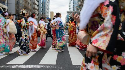 Photo of several women in Kimono crossing a busy street