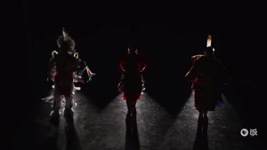 Still image from the video showing silhouettes of the three dancers against a black backdrop