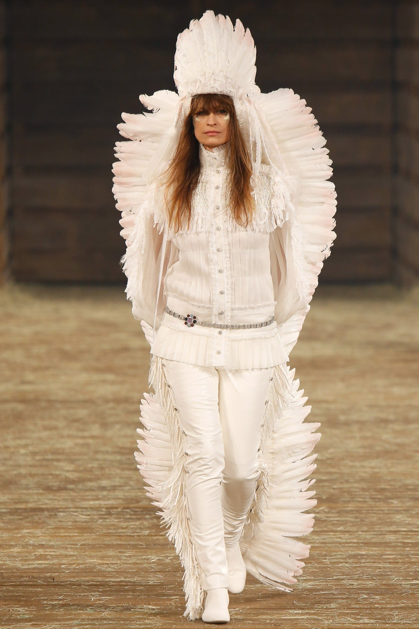 Model Carolin de Maigret walking down the runway in a white outfit and large white feathered headdress