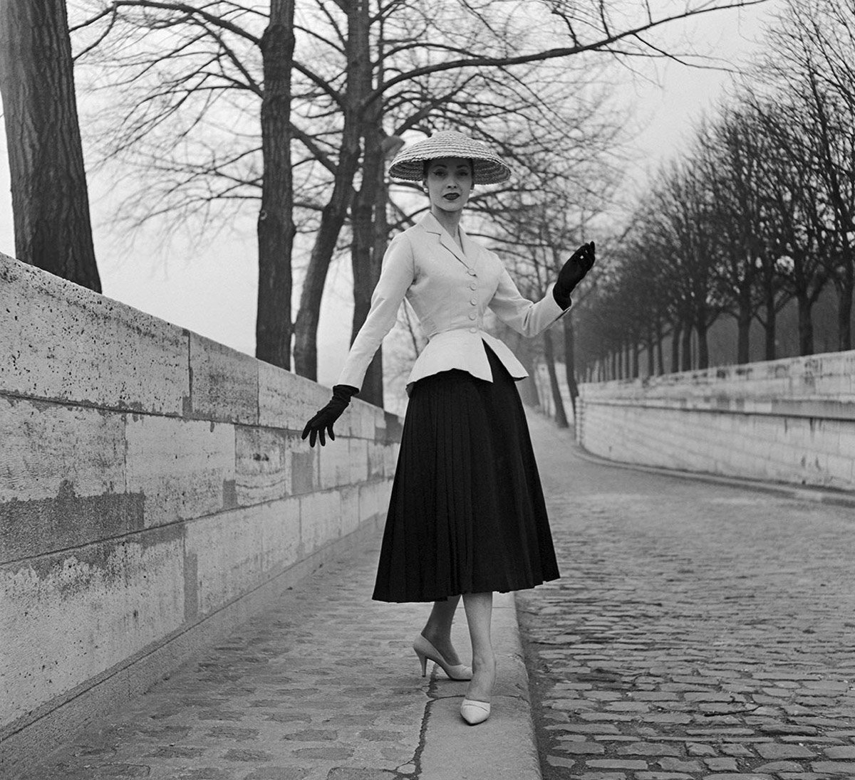 Black and white photograph of the Christian Dior New Look on a model posing in a tree-lined street