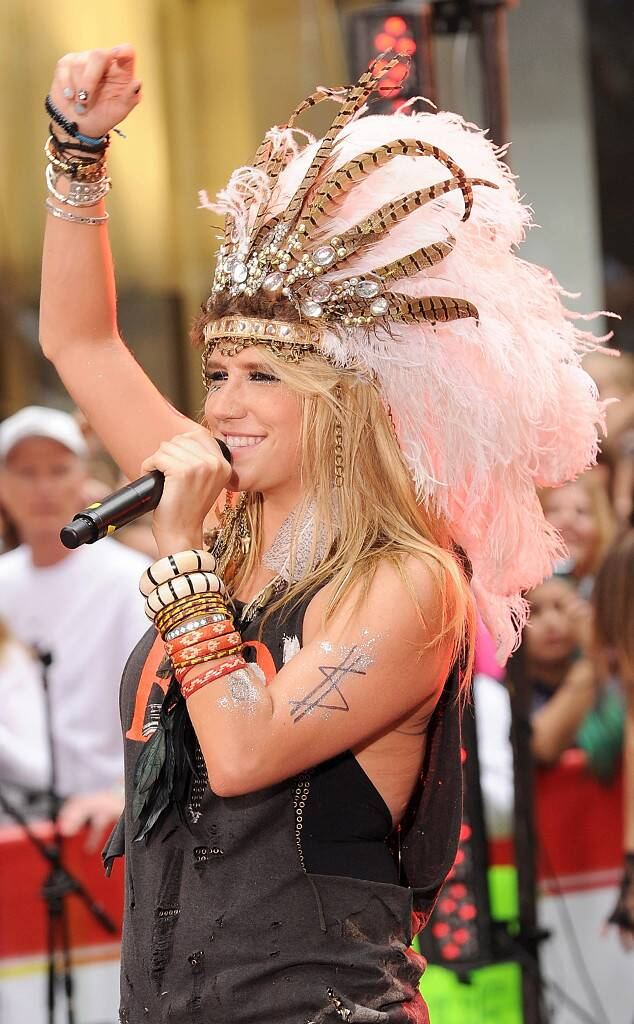 Image of Kesha at a performance wearing a bejeweled Native American inspired feather headdress