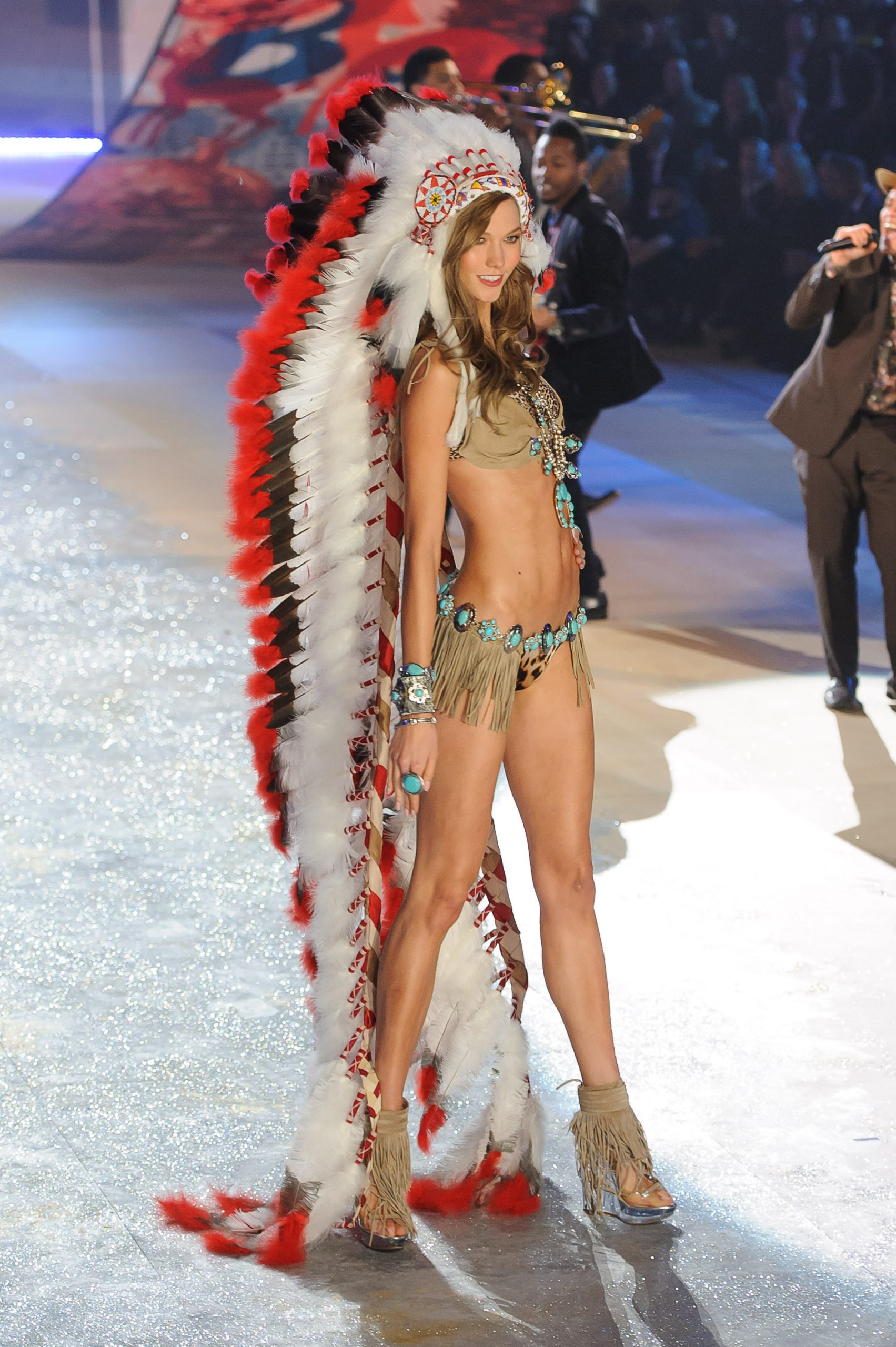Karlie Kloss posing at the end of the Victorias Secret fashion show runway in Native American inspired underwear and a long trailing feather headdress