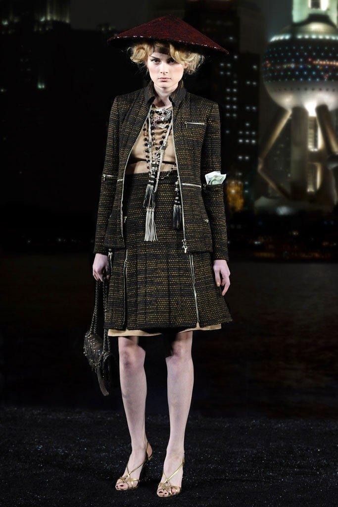 Runway photograph of a white model from Chanel Pre-fall Shanghai wearing a brown skirt suit and burgundy non la hat