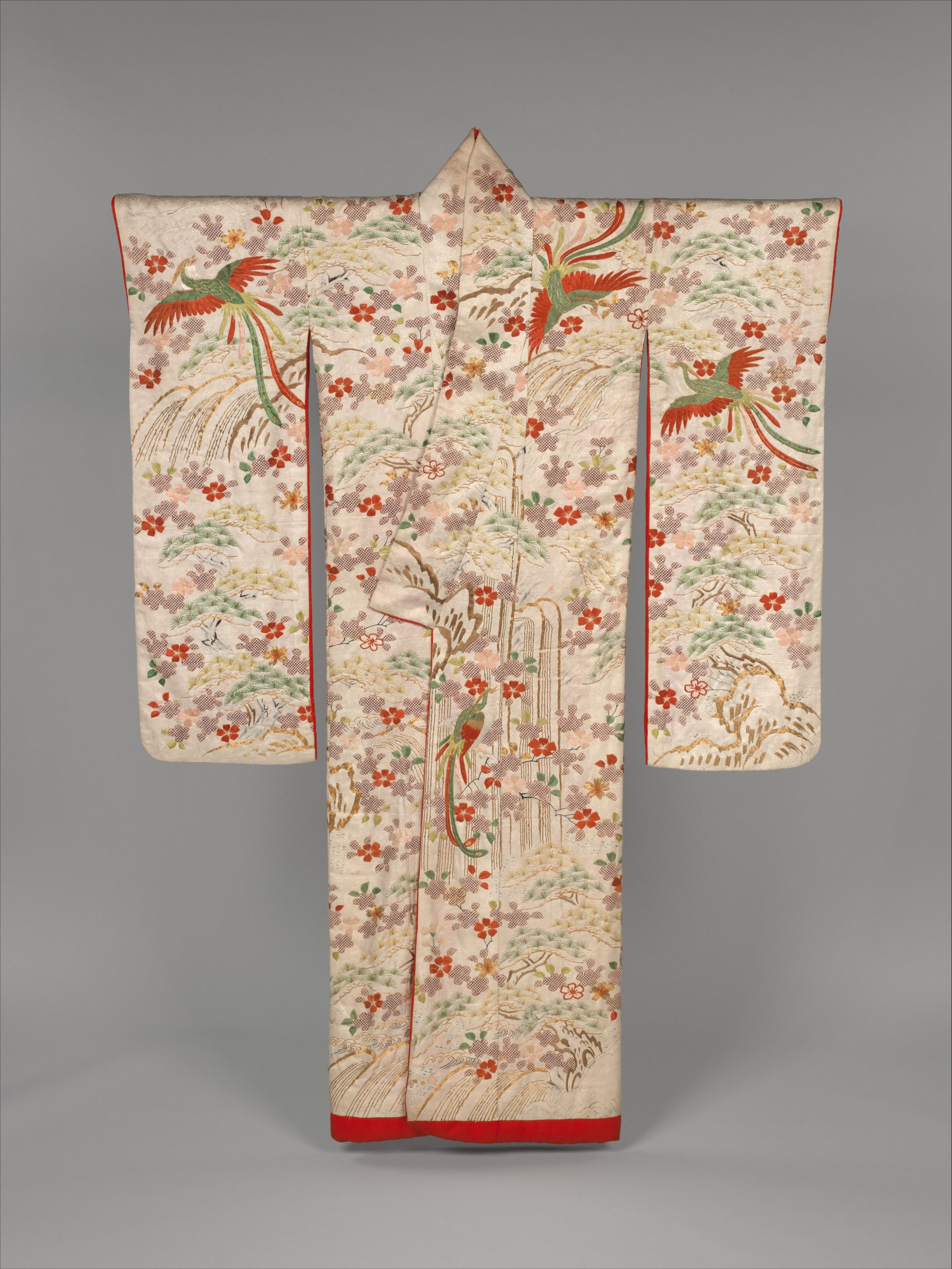 Photograph of a red and cream coloured richly embroidered Kimono displayed on a T-bar hanger