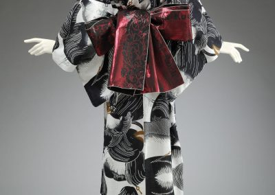 Photo of the back of a black and white printed Kimono with a Red patterned Obi sash tied in a bow. The Kimono is displayed on a mannequin.