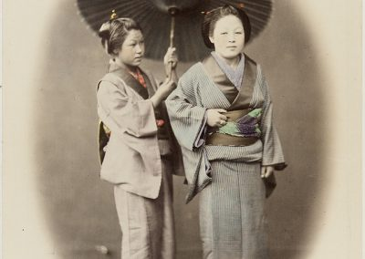 A hand coloured black and white photograph of two young Japanese women in Kimonos, the woman on the left holds an umbrella