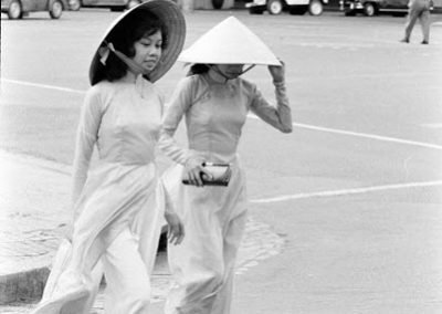 Black and white photograph of two Vietnamese women crossing the street wearing traditional dress and non la