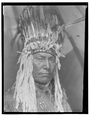 Black and white portrait photograph of a Native American man in a tall upright feather headdress