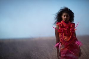 Exhibition feature image of an indigenous model in a contemporary red garment standing in a field
