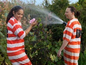Photo of two female inmates in the garden. The female on the right is spraying the female on the left with a garden hose