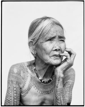 Portrait of old woman adorned with tattos across her shoulder looking towards the left with her head in her hand.